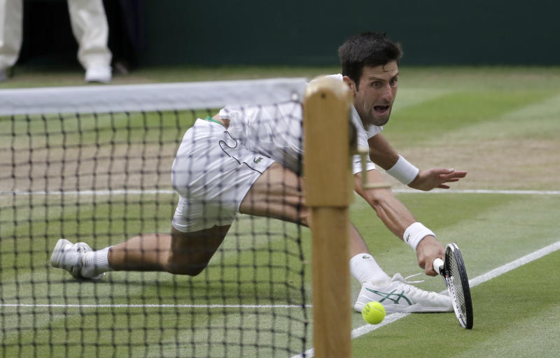 Serbia's Novak Djokovic returns the ball to Rafael Nadal of Spain during their men's singles semifinals match at the Wimbledon Tennis Championships, in London, Saturday July 14, 2018.(AP Photo/Ben Curtis)