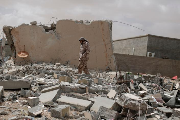 A soldier loyal to the 'Libyan Dawn' movement looks at damage caused by an air strike at a house in Bin Jawad, the last town before the frontline near Sidra, a key oil terminal in Libya than is currently contested by the country's two opposing governments, on March 7, 2015. (Photo: Sam Tarling/Corbis via Getty Images)