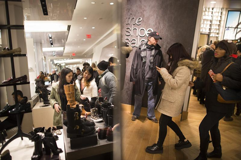 Customers are reflected in a mirror in the shoe section of the Macy's Herald Square flagship store, Thursday, Nov. 28, 2013, in New York. Instead of waiting for Black Friday, which is typically the year's biggest shopping day, more than a dozen major retailers are opening on Thanksgiving this year. (AP Photo/John Minchillo)