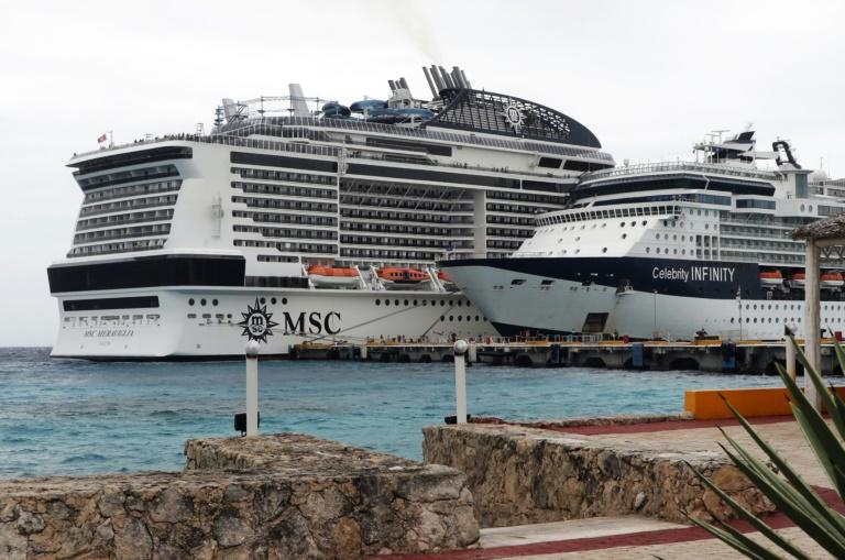 The MSC Meraviglia cruise ship (L) is seen in Cozumel, Mexico, after both Jamaica and the Cayman Islands refused to allow it to dock over fears of the new coronavirus (AFP Photo/JOSE CASTILLO)