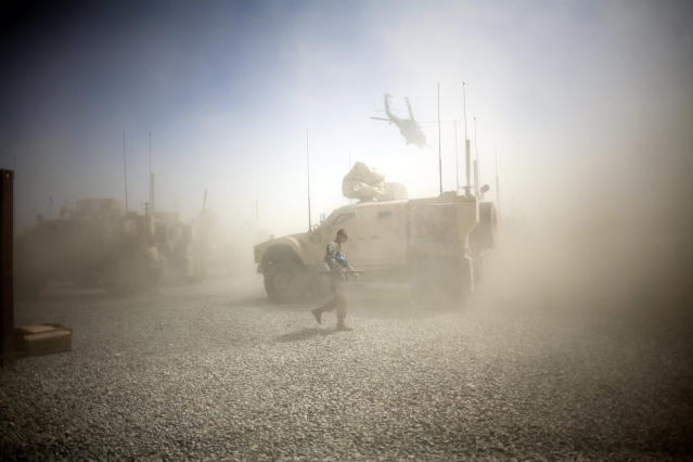 <p>A U.S. Army soldier takes cover from dust whipped up by a departing helicopter at Combat Outpost Terra Nova in Kandahar, Afghanistan, July 19, 2010. </p>