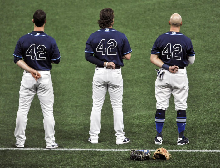 From left to right, Tampa Bay Rays' Joey Wendle, Brett Phillips and Mike Brosseau wear No. 42 on their jerseys in honor of Jackie Robinson Day before a baseball game against the Texas Rangers, Thursday, April 15, 2021, in St. Petersburg, Fla. (AP Photo/Steve Nesius)