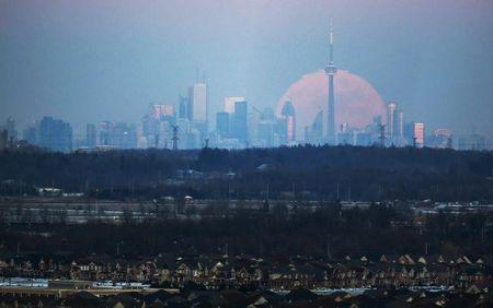 The moon rises over the Toronto city skyline as seen from Milton, Ontario