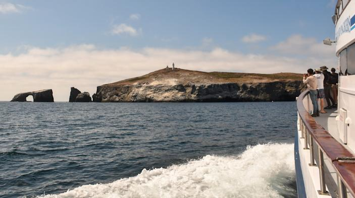 """Passengers look to Anacapa Island's iconic arched-rock formation on an Island Packers trip from Oxnard. <span class=""""copyright"""">(Christopher Reynolds / Los Angeles Times)</span>"""