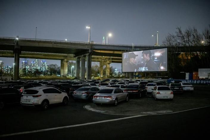 People can park their cars in front of a large outdoor screen (AFP Photo/Ed JONES)