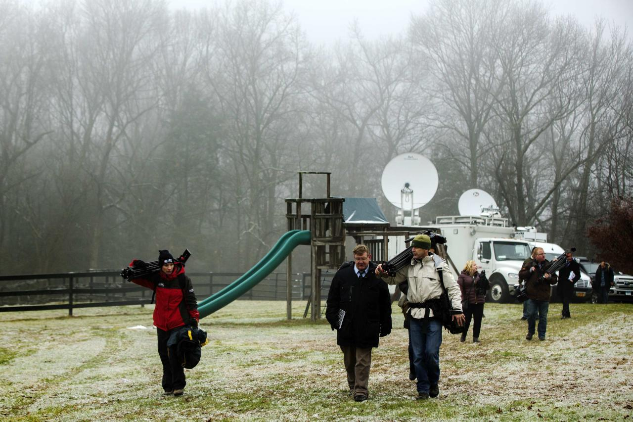 Members of the media depart after an announcement by family members of victims killed in the Sandy Hook Elementary School shooting about the formation of the website mysandyhookfamily.org created for victim's families in Sandy Hook, Connecticut December 9, 2013. The Connecticut town of Newtown on Monday asked for privacy and a restrained media presence ahead of the anniversary of the shooting that killed 20 children and six adults at Sandy Hook Elementary School. REUTERS/Lucas Jackson (UNITED STATES - Tags: CRIME LAW ANNIVERSARY)