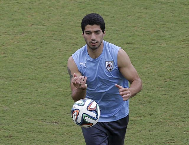 Uruguay's Luis Suarez runs on the pitch during a training session the day before the team's next group D World Cup soccer match, at the Arena das Dunas in Natal, Brazil, Monday, June 23, 2014. (AP Photo/Antonio Clanni)