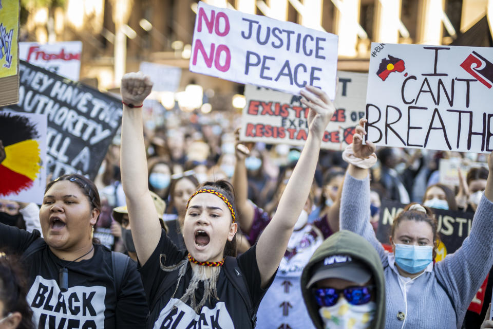 Protesters display posters at the rally in Brisbane on Saturday. Source: AAP
