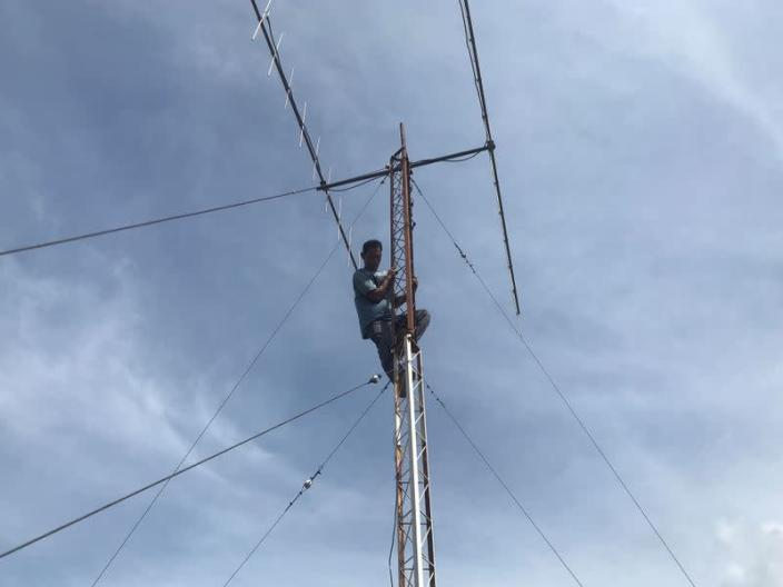 Munandar, radio communication technician, climbs as he checks tower in Banda Aceh