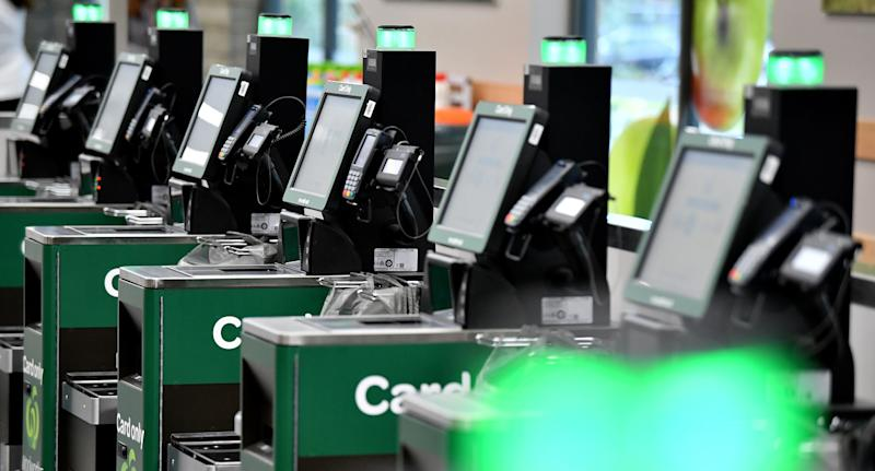 Photo shows a row of self-service checkouts in Woolworths.
