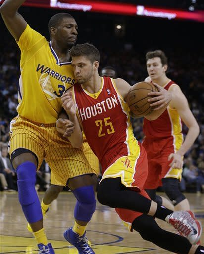 Houston Rockets' Chandler Parsons, right, drives the ball against Golden State Warriors' Festus Ezeli during the first half of an NBA basketball game Friday, March 8, 2013, in Oakland, Calif. (AP Photo/Ben Margot)