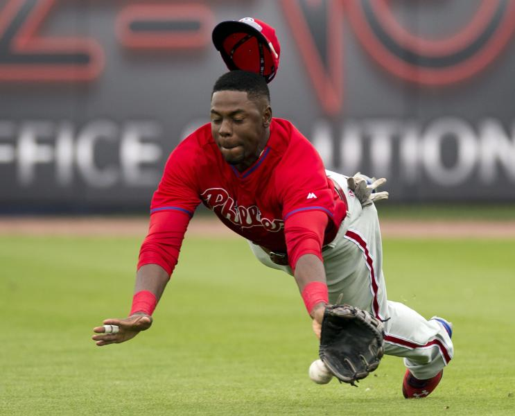 Philadelphia Phillies right fielder John Mayberry dives for a single by Toronto Blue Jays' Edwin Encarnacion during the fifth inning of an exhibition baseball game in Dunedin, Fla., Thursday Feb. 27, 2014. (AP Photo/The Canadian Press, Frank Gunn)