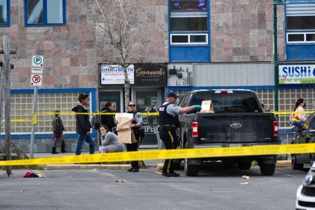 RCMP gather and bag evidence at a taped-off crime scene in downtown Yellowknife late Wednesday afternoon. (Walter Strong/CBC - image credit)