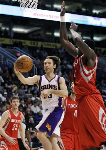 Phoenix Suns' Steve Nash, center, passes the ball off to a teammate as Houston Rockets' Samuel Dalembert, right, of Haiti, defends as Rockets' Chandler Parsons (25) and Luis Scola (4), of Argentina, look on during the first quarter in an NBA basketball game, Sunday, March 18, 2012, in Phoenix. (AP Photo/Ross D. Franklin)