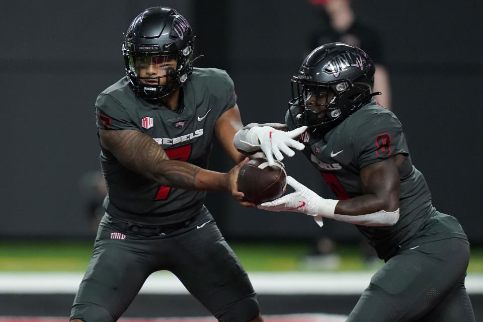 UNLV quarterback Cameron Friel (7) hands the ball off to running back Charles Williams (8) during the first half of an NCAA college football game against the Iowa State, Saturday, Sept. 18, 2021, in Las Vegas. (AP Photo/John Locher)