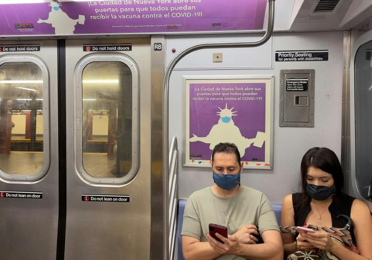 Travelers wearing masks sit in the subway where posters advertise free Covid-19 vaccination in New York City in several languages on July 18, 2021 (AFP/Daniel SLIM)