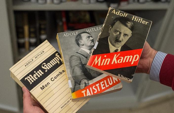 """A man holds a French (L), a Finnish (C) and a Danish (R) edition of Adolf Hitler's """"Mein Kampf"""" (My Struggle) at the Institute for Contemporary History in Munich (AFP Photo/Matthias Balk)"""