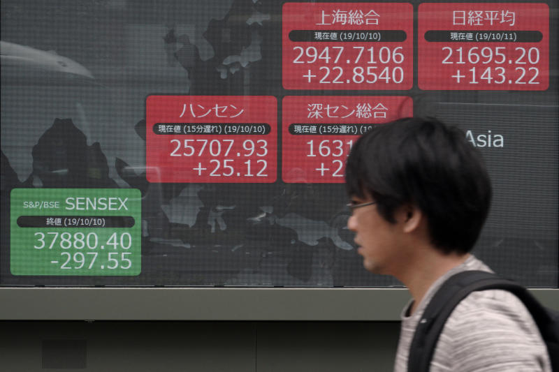 In this Oct. 11, 2019, photo, a man walks past an electronic stock board showing Japan's Nikkei 225 index and other Asian market index at a securities firm in Tokyo. Asian shares were mixed Monday, Oct. 21,  amid uncertainties about Britain's exit from the European Union and the ongoing trade conflict  (AP Photo/Eugene Hoshiko)