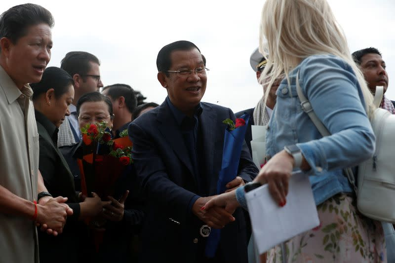 Cambodia's Prime Minister Hun Sen welcomes a passenger of MS Westerdam, a cruise ship that spent two weeks at sea after being turned away by five countries over fears that someone aboard might have the coronavirus , as it docks in Sihanoukvil