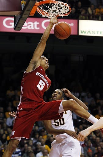 Wisconsin's Ryan Evans (5) dunks the ball over Minnesota's Ralph Sampson III (50) during the first half of an NCAA college basketball game Thursday, Feb. 9, 2012, in Minneapolis. (AP Photo/Genevieve Ross)