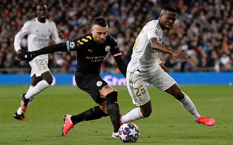 Manchester City's Argentinian defender Nicolas Otamendi (L) vies with Real Madrid's Brazilian forward Vinicius Junior during the UEFA Champions League round of 16 first-leg football match between Real Madrid CF and Manchester City - PIERRE-PHILIPPE MARCOU/AFP via Getty Images