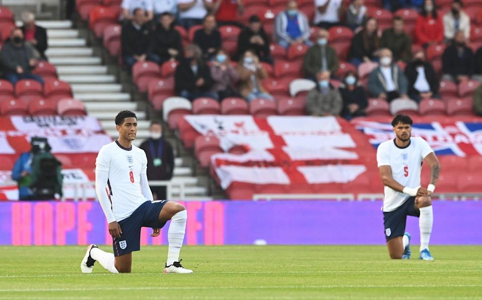 Jude Bellingham and Tyrone Mings take the knee ahead of England's warm-up friendly against Austria - GETTY IMAGES
