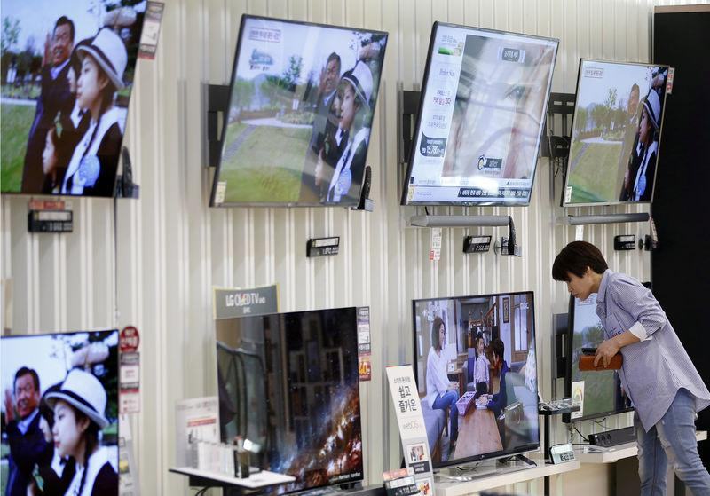 FILE PHOTO: A woman looks at a LG Electronics' OLED TV at its store in Seoul