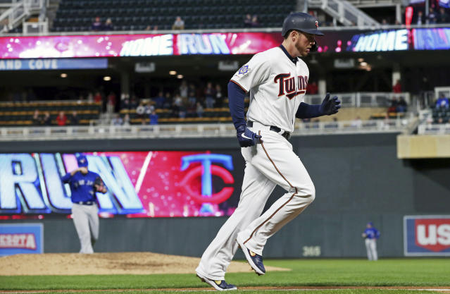 Minnesota Twins' C.J. Cron, right, jogs home on a three-run home run off Toronto Blue Jays pitcher Matt Shoemaker, back left, in the fourth inning of a baseball game Monday, April 15, 2019, in Minneapolis. (AP Photo/Jim Mone)