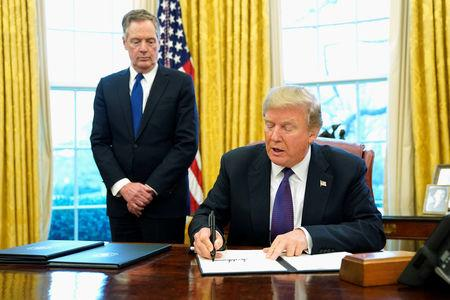 U.S. President Donald Trump, flanked by U.S. Trade Representative Robert Lighthizer, signs a directive to impose tariffs on imported washing machines in the Oval Office at the White House in Washington, U.S. January 23, 2018.  REUTERS/Jonathan Ernst
