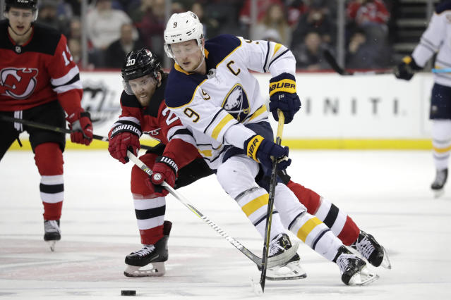 Buffalo Sabres center Jack Eichel (9) skates against New Jersey Devils center Blake Coleman (20) during the first period of an NHL hockey game, Monday, March 25, 2019, in Newark, N.J. (AP Photo/Julio Cortez)