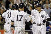 New York Yankees' Ichiro Suzuki (31), Jayson Nix (17) and Derek Jeter, rear right, congratulate Nick Swisher, right, on his fourth-inning grand slam off Toronto Blue Jays relief pitcher Brad Lincoln in their baseball game at Yankee Stadium in New York, Thursday, Sept. 20, 2012. (AP Photo/Kathy Willens)