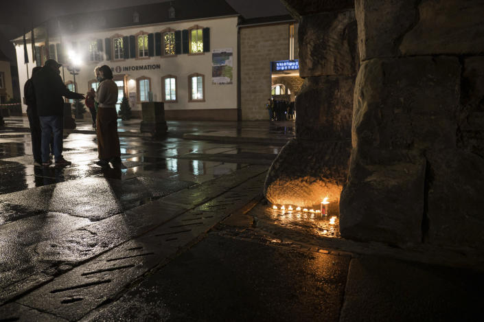 People lit candles at the historic Porta Nigra gate near the scene of an incident in Trier, Germany, Tuesday, Dec. 1, 2020. German police say people have been killed and several others injured in the southwestern German city of Trier when a car drove into a pedestrian zone. Trier police tweeted that the driver had been arrested and the vehicle impounded.( Oliver Dietze/dpa via AP)