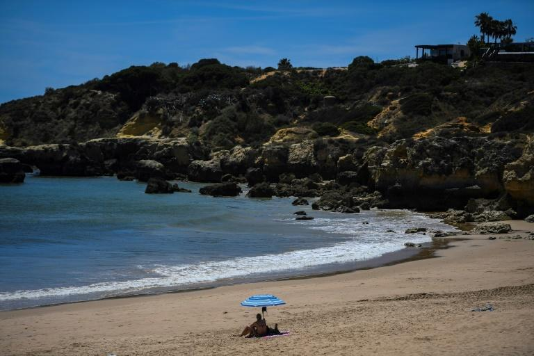 A woman sits under a beach umbrella at Oura beach. Restaurant owners and others hailed the restart of tourism, but some were cautious