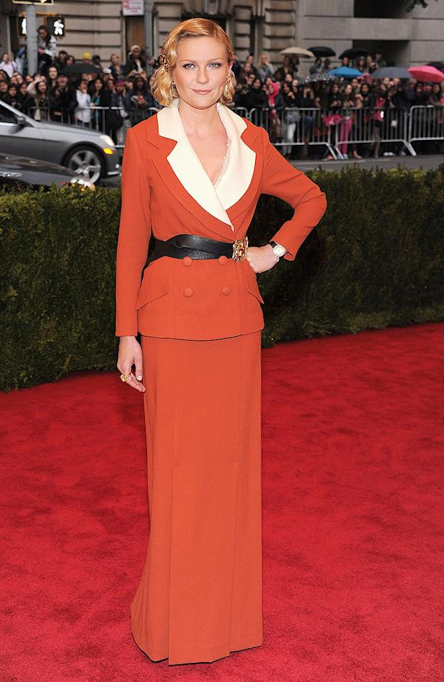 """<p class=""""MsoNoSpacing"""">Kirsten Dunst stood out in an unconventional choice: a custom Rodarte pumpkin and cream wool jacket over a pumpkin-colored skirt, with a black belt cinched at her waist.</p>"""