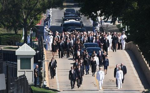 Family and friends join a procession behind McCain's casket - Credit: Mary Calvert/Reuters