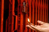 A Bharatiya Janata Party (BJP) activist performs a Hindu ritual in front of the closed gate of a Ram Temple in Kolkata on August 5, 2020, to mark the groundbreaking ceremony of the Ram Temple in Ayodhaya. - India's Prime Minister Narendra Modi will lay the foundation stone for a grand Hindu temple in a highly anticipated ceremony on August 5 at a holy site that was bitterly contested by Muslims, officials said. The Supreme Court ruled in November 2019 that a temple could be built in Ayodhya, where Hindu zealots demolished a 460-year-old mosque in 1992. (Photo by Dibyangshu SARKAR / AFP) (Photo by DIBYANGSHU SARKAR/AFP via Getty Images)