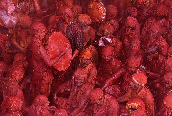 """In this photograph taken on March 6, 2017, Indian devotees covered in coloured powder look on as a drummer plays during celebrations for Lathmar Holi in Barsana on the outskirts of Mathura in the northern Indian state of Uttar Pradesh. Lathmar Holi is a local celebration of the Hindu festival of Holi, usually some days ahead of the actual festival - it translates as 'that Holi in which people hit with sticks""""."""