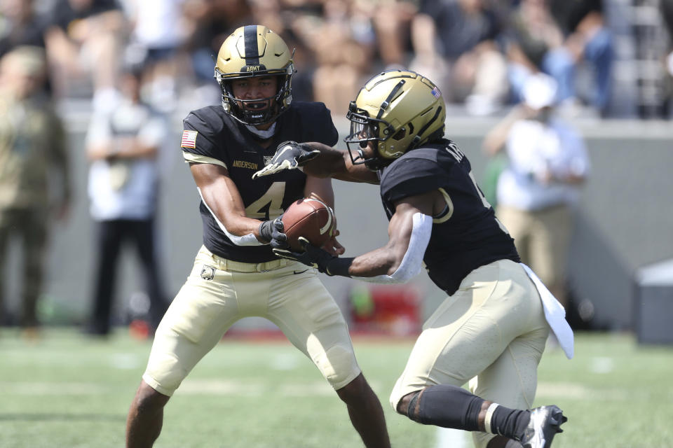 FILE - Army quarterback Christian Anderson (4) hands the ball off to running back A.J. Howard (5) during an NCAA football game in West Point, N.Y., in this Saturday, Sept. 11, 2021, file photo. No team in the country runs the ball a greater percentage of the time than Army. No team does a better job of stopping the run than Wisconsin. That sets up an intriguing matchup Saturday night, Oct. 16. (AP Photo/Vera Nieuwenhuis, File)