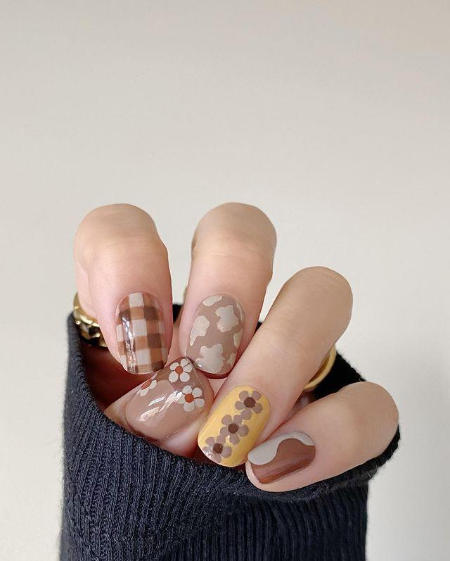 "<p>Multi-print <a href=""https://www.cosmopolitan.com/style-beauty/beauty/g34696587/aquarius-nail-art-ideas/"" rel=""nofollow noopener"" target=""_blank"" data-ylk=""slk:nail art"" class=""link rapid-noclick-resp"">nail art</a> is having a moment. The only rule? Keep the color palette in the same family (NGL, I love this muted beige vibe). To get the look, use a few different <a href=""https://www.mentedcosmetics.com/products/nude-nail-lacquer?_pos=1&_sid=86c304628&_ss=r"" rel=""nofollow noopener"" target=""_blank"" data-ylk=""slk:neutral-colored polishes"" class=""link rapid-noclick-resp"">neutral-colored polishes</a> to freehand different designs on each nail, or you can take the easier route and mix and match some <a href=""https://www.cosmopolitan.com/style-beauty/beauty/a28440873/olive-june-nail-stickers-review/"" rel=""nofollow noopener"" target=""_blank"" data-ylk=""slk:nail stickers"" class=""link rapid-noclick-resp"">nail stickers</a> instead. </p><p><a href=""https://www.instagram.com/p/CII-fSPHmoH/?utm_source=ig_embed&utm_campaign=loading"" rel=""nofollow noopener"" target=""_blank"" data-ylk=""slk:See the original post on Instagram"" class=""link rapid-noclick-resp"">See the original post on Instagram</a></p>"