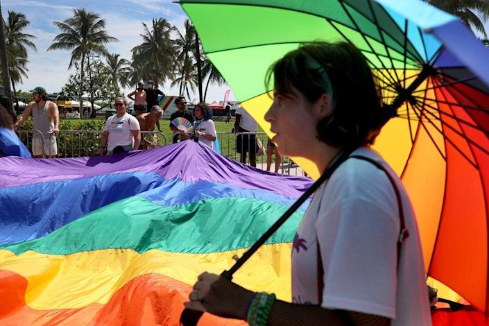 People carry the rainbow flag as they participate in the Miami Beach Pride Parade along Ocean Drive on 19 September 2021 in Miami Beach, Florida (Getty Images)