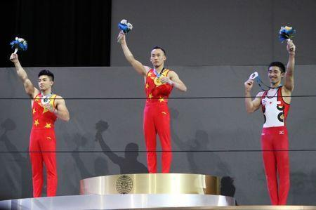 Oct 3, 2017; Montreal, Quebec, CAN; Chaopan Lin of People's Republic of China (left) and Ruoteng Xiao of People's Republic of China (center) and Kenzo Shirai of Japan (right) respectively finishes second and first and third at the Men's Individual All-Around Final during the 47th FIG Artistic Gymnastics World Championship at Montreal Olympic Stadium. Mandatory Credit: Jean-Yves Ahern-USA TODAY Sports