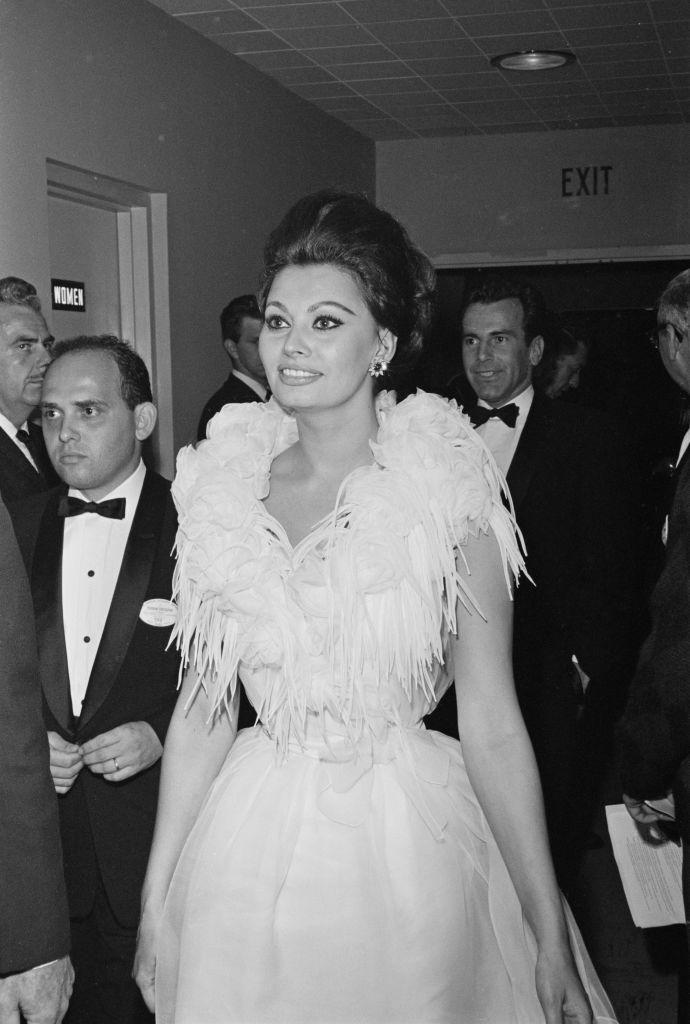 <p>The Italian actress went all out in this feathered white gown, but kept the focus on the bodice by keeping her accessories minimal. She starred in <em>Yesterday, Today, and Tomorrow</em> this year, which won the Academy Award for Best Foreign Language Film. </p>