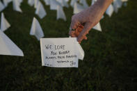 """Zoe Nassimoff, of Argentina, holds a white flag that is part of artist Suzanne Brennan Firstenberg's temporary art installation, """"In America: Remember,"""" in remembrance of Americans who have died of COVID-19, on the National Mall in Washington, Friday, Sept. 17, 2021. Nassimoff wrote on the flag in memory of her grandparent who lived in Florida and died from COVID-19. (AP Photo/Brynn Anderson)"""
