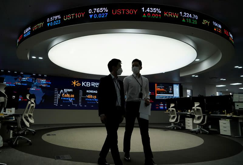 Currency dealers walk past an electronic board showing the Korea Composite Stock Price Index (KOSPI) at a dealing room of a bank in Seoul