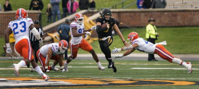 Missouri quarterback Drew Lock, center, runs between Florida defenders during the first half of an NCAA college football game Saturday, Nov. 4, 2017, in Columbia, Mo. (AP Photo/L.G. Patterson)