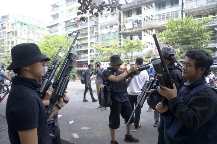 Anti-coup protesters stand guard with homemade air rifle during a protest in Yangon, Myanmar, Saturday, April 3, 2021. Threats of lethal violence and arrests of protesters have failed to suppress daily demonstrations across Myanmar demanding the military step down and reinstate the democratically elected government.(AP Photo)