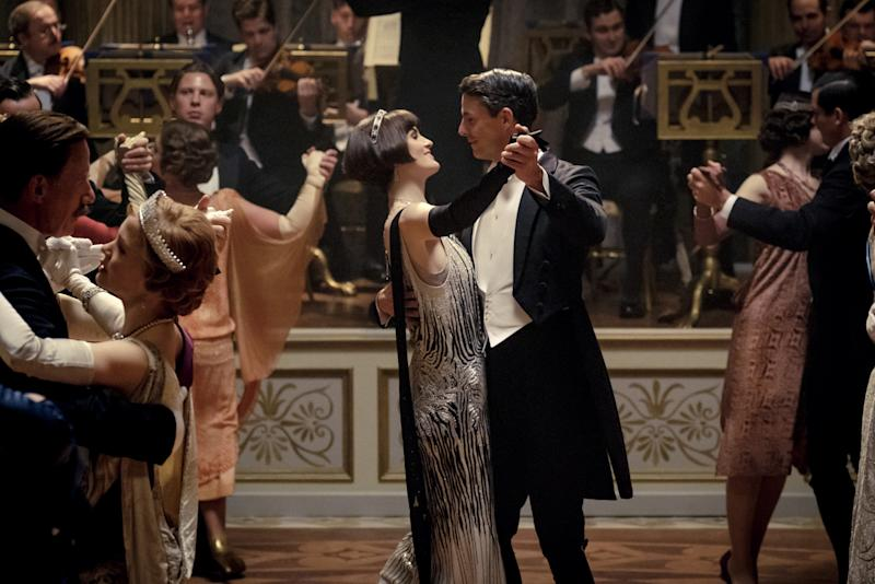 Michelle Dockery and Matthew Goode dressed in a silver gown and black suit dancing in a ballroom on the set of the new Downton Abbey movie