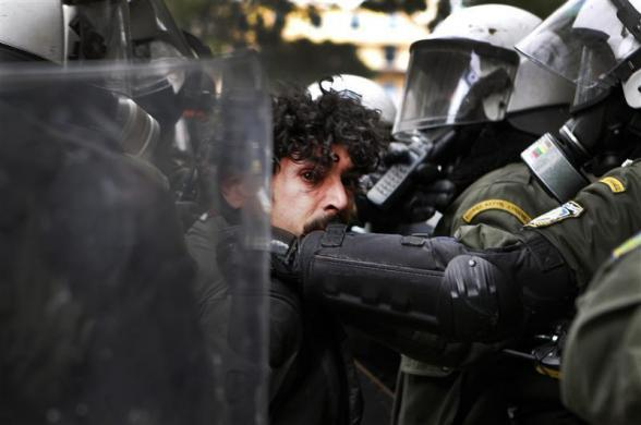 A demonstrator is detained by riot police during protests in Athens's Syntagma (Constitution) square against planned reforms by Greece's coalition government, February 10, 2012.