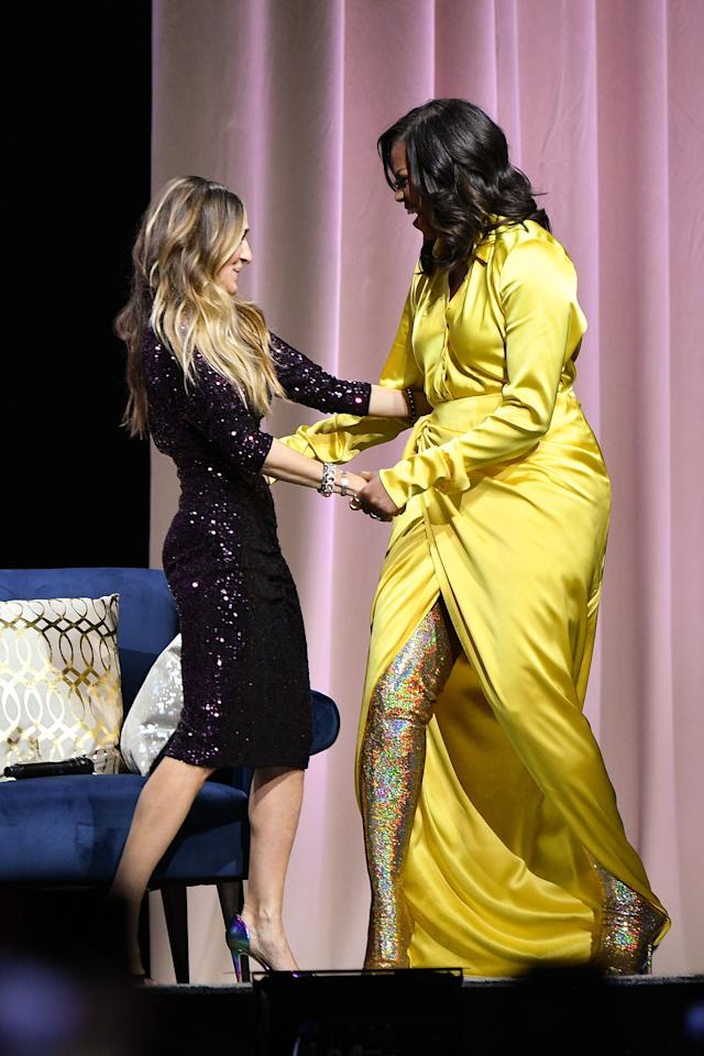 "<p>Wearing a bright yellow dress and <a href=""https://www.popsugar.com/fashion/Michelle-Obama-Balenciaga-Boots-December-2018-45620220"" class=""ga-track"" data-ga-category=""Related"" data-ga-label=""https://www.popsugar.com/fashion/Michelle-Obama-Balenciaga-Boots-December-2018-45620220"" data-ga-action=""In-Line Links"">thigh-high gold Balenciaga boots</a>.</p>"