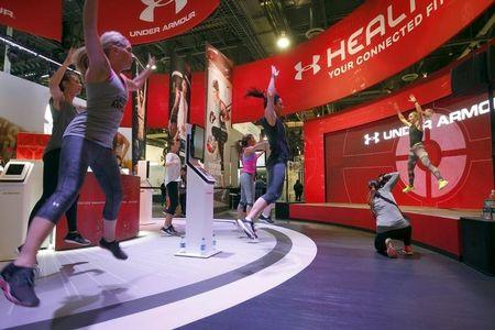 People work out at the Under Armour booth as the company promotes the Health Box, a Connected Fitness system, during the 2016 CES trade show in Las Vegas, Nevada